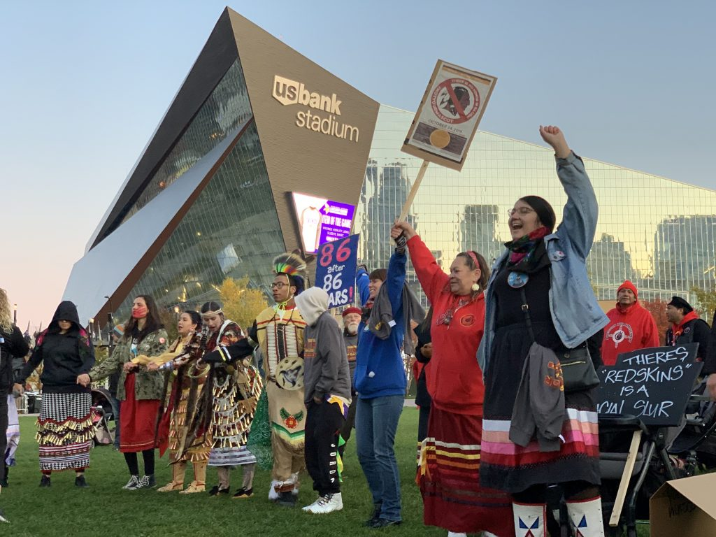 Indigenous people hold protest signs against racist sports mascots in front of US Bank Stadium
